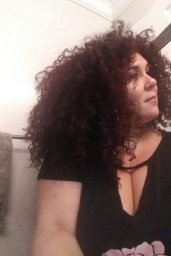 A woman showing her curly hair after using the blow dryer diffuser