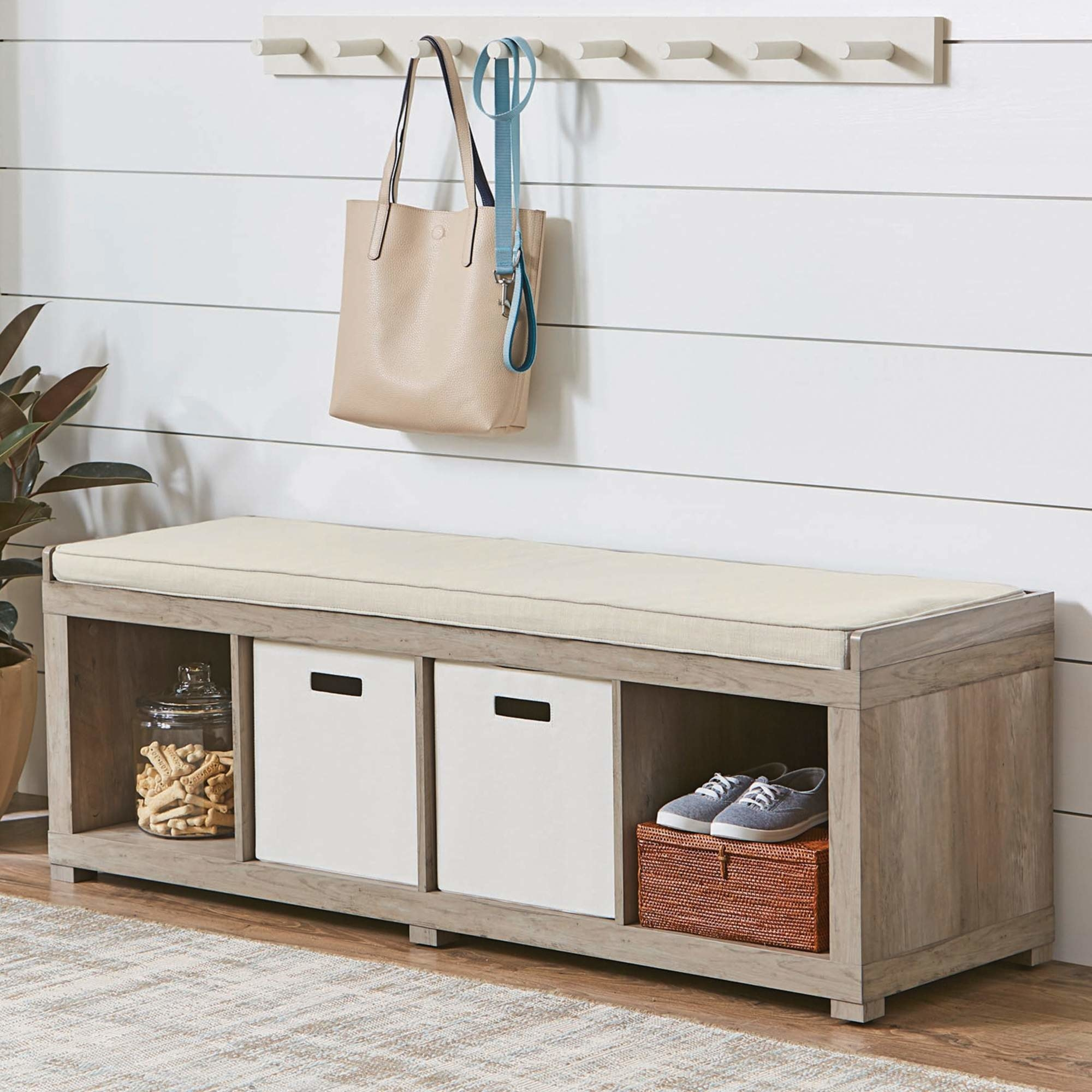 gray cushioned storage bench with cube and items stored inside