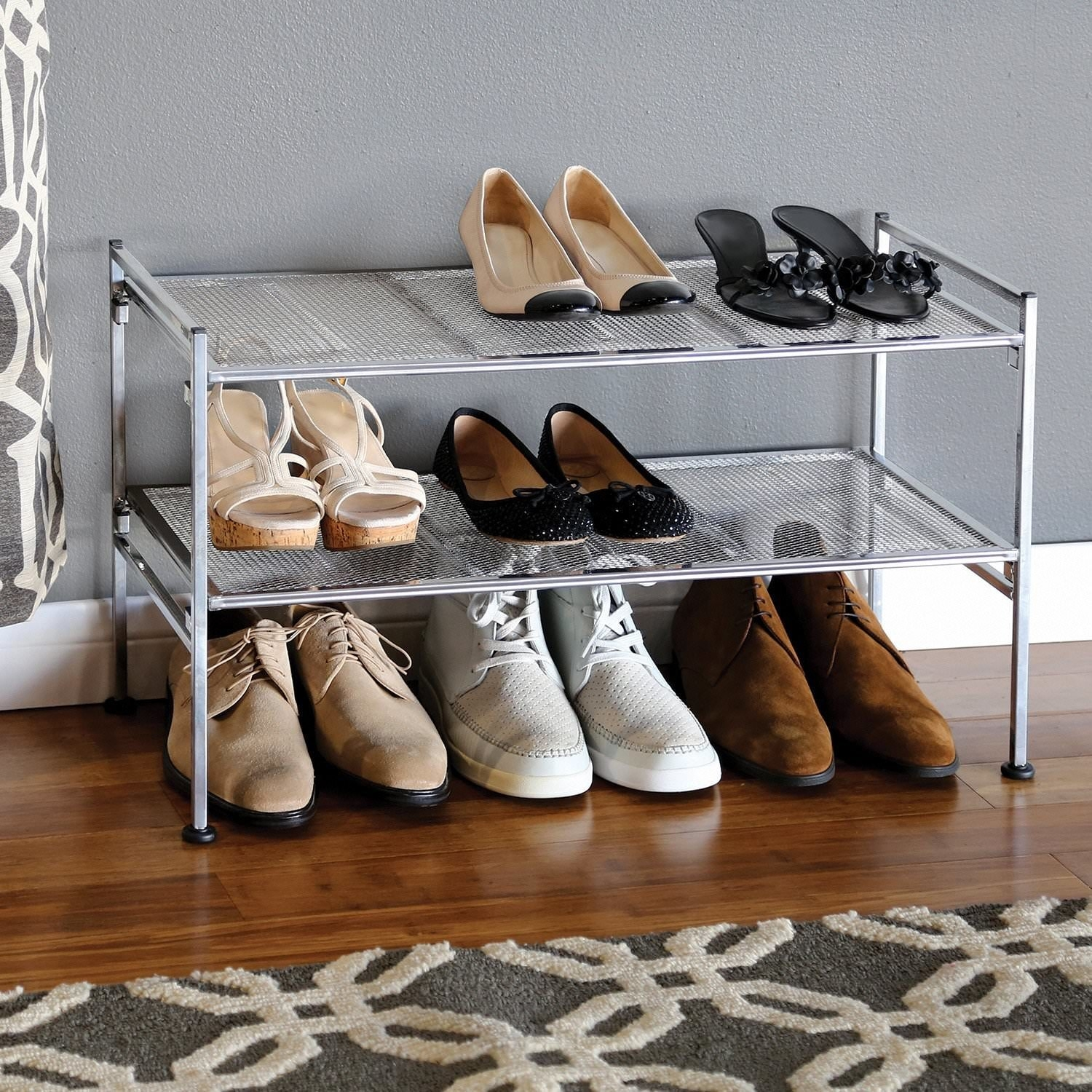 two-tiered iron shoe rack against a wall with shoes under and on the shelves