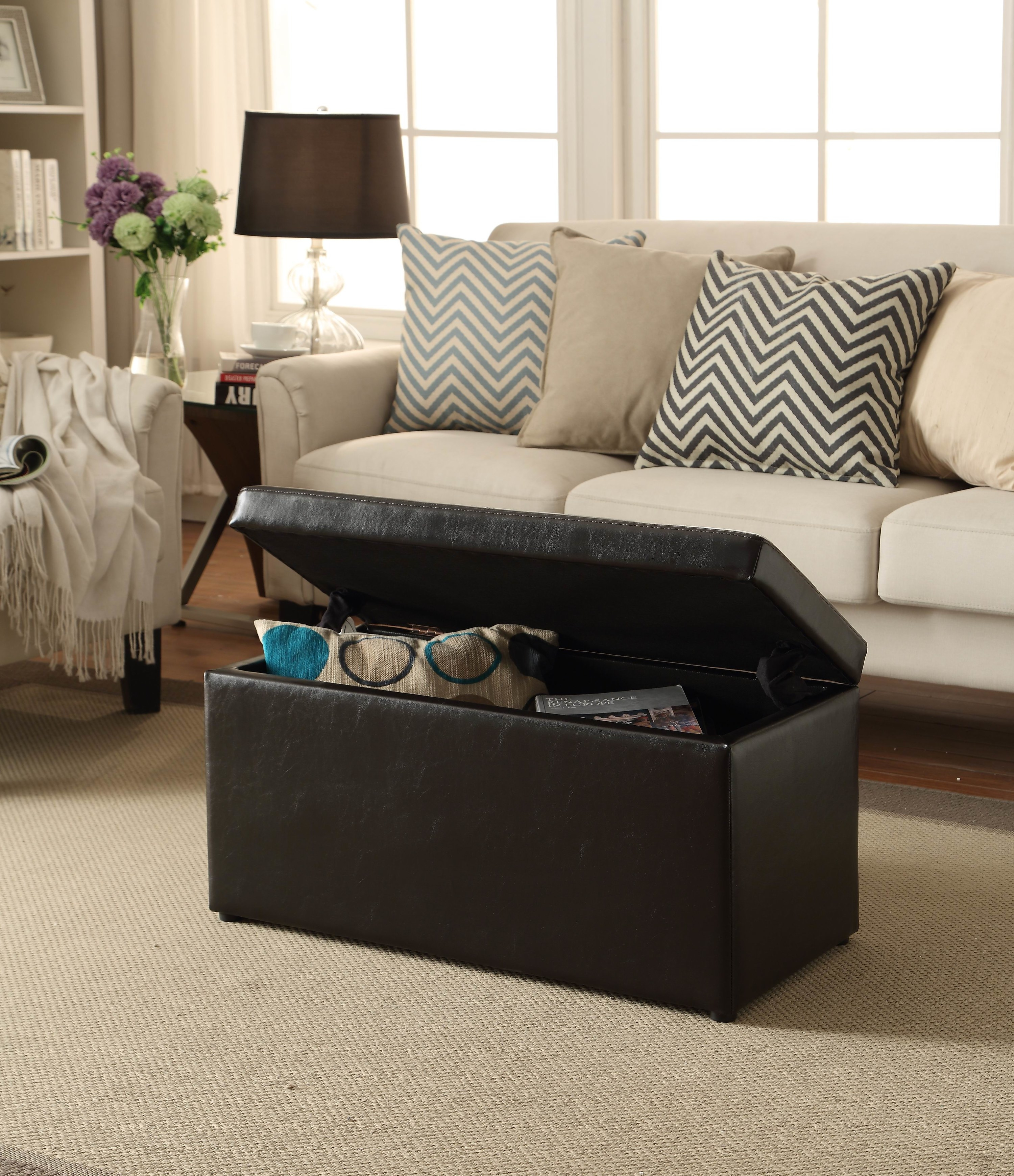 brown storage ottoman with lid open and miscellaneous items inside