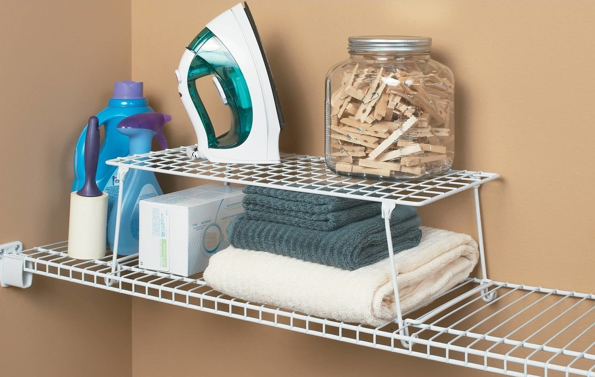 white wire storage shelf holding an iron and jar of clothes pins with towels underneath