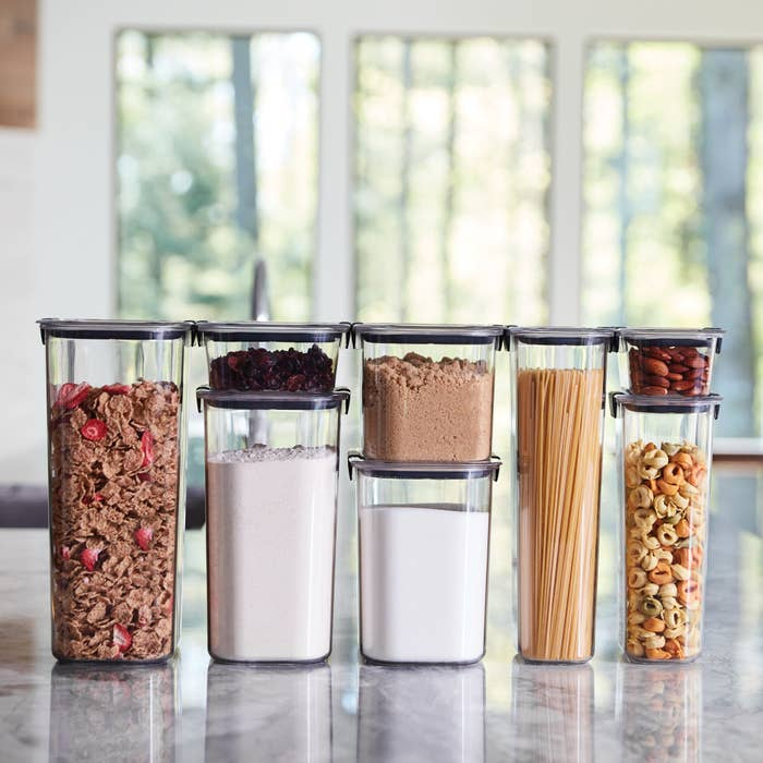 clear food storage containers filled with various dry foods like cereal, flour, and pasta