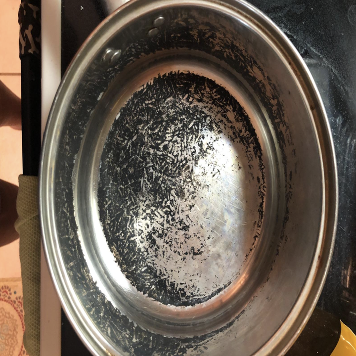 a reviewer photo of a pot with black burnt bits on the bottom