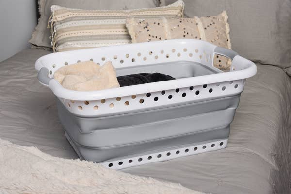 white and gray collapsible laundry basket sitting on a bed