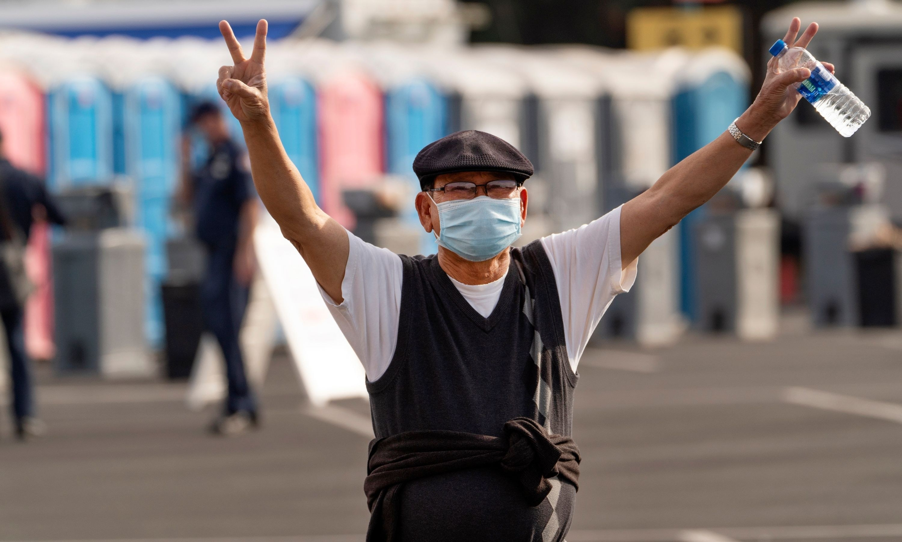 a newly vaccinated man throws peace signs in the air gleefully