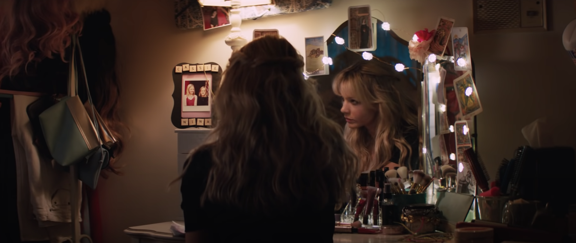 Cassie sitting in front of a mirror decorated with photographs
