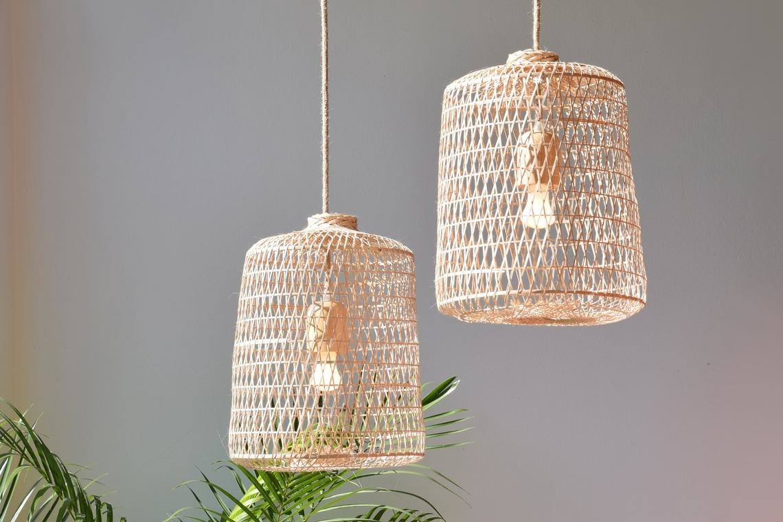 Two exposed bulbs hanging from a ceiling covered by basket-like woven shades