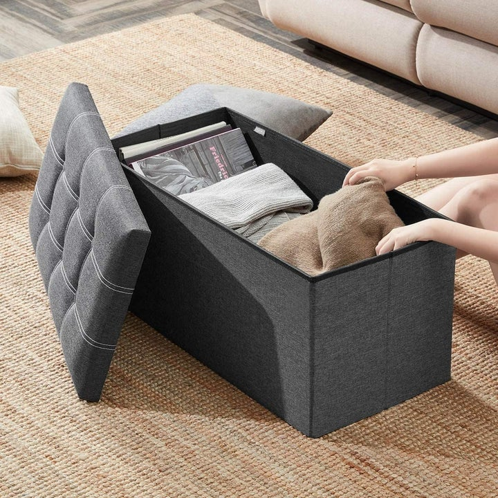 model pulling a blanket out of the storage ottoman