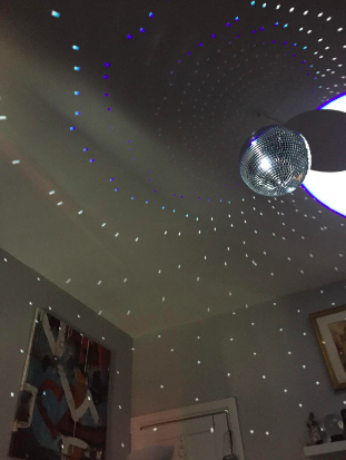 Reviewer with large disco ball on ceiling, the light hitting it causes dots to hit the walls around the room