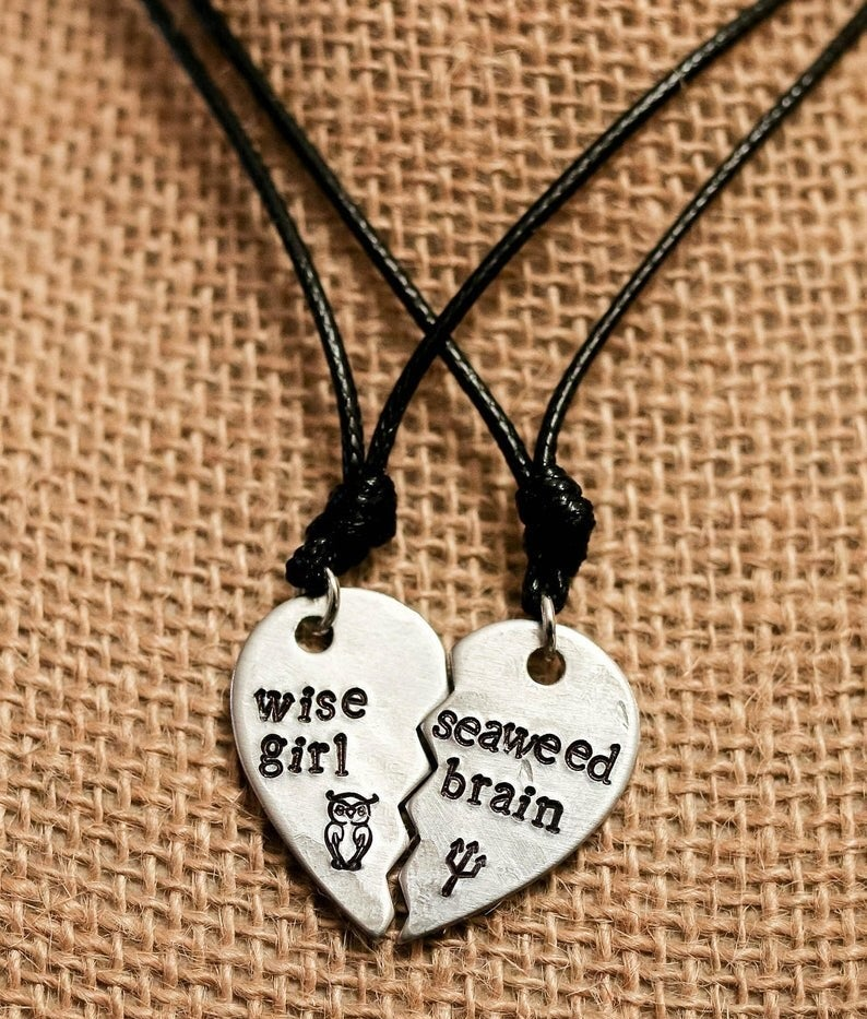 """The silver half heart pendants on black cords that fit together. One says """"Wise girl"""" with an owl symbol and the other """"Seaweed brain"""" with a trident"""