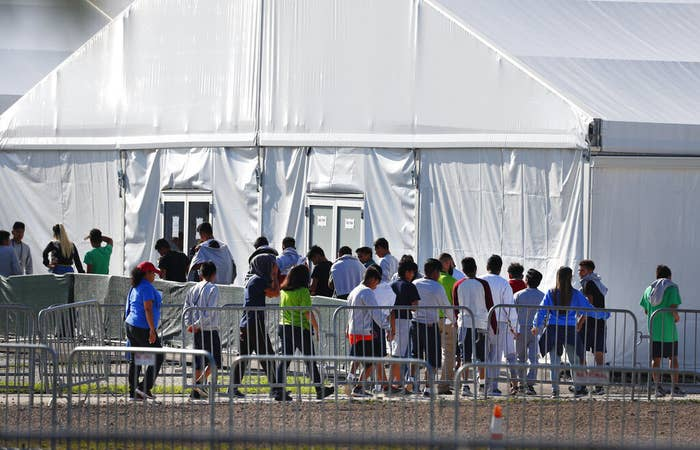 People line up in single file outside a large white tent
