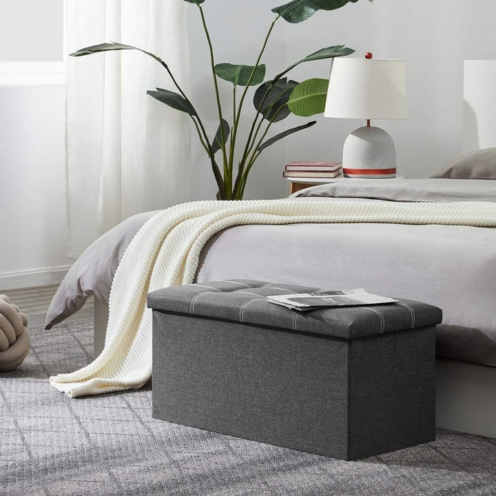 gray ottoman at the foot of a bed