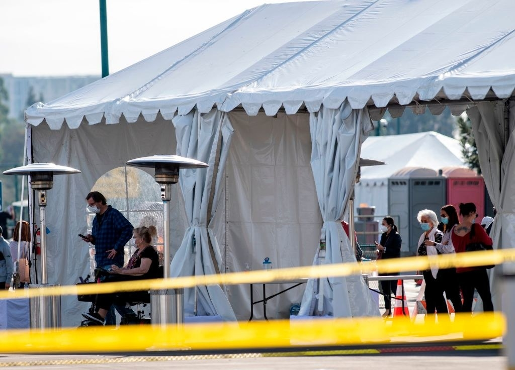 people are seated inside the tents as their vaccines are administered