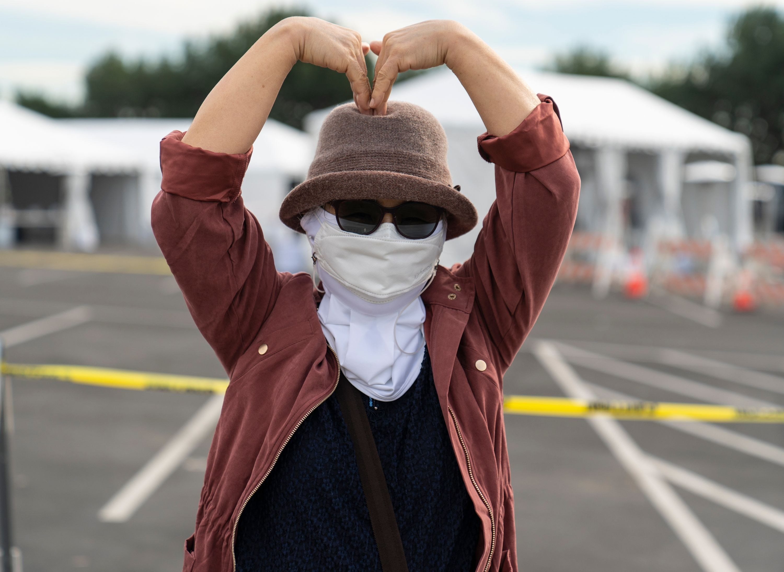a woman makes a heart with her arms outside the distribution site