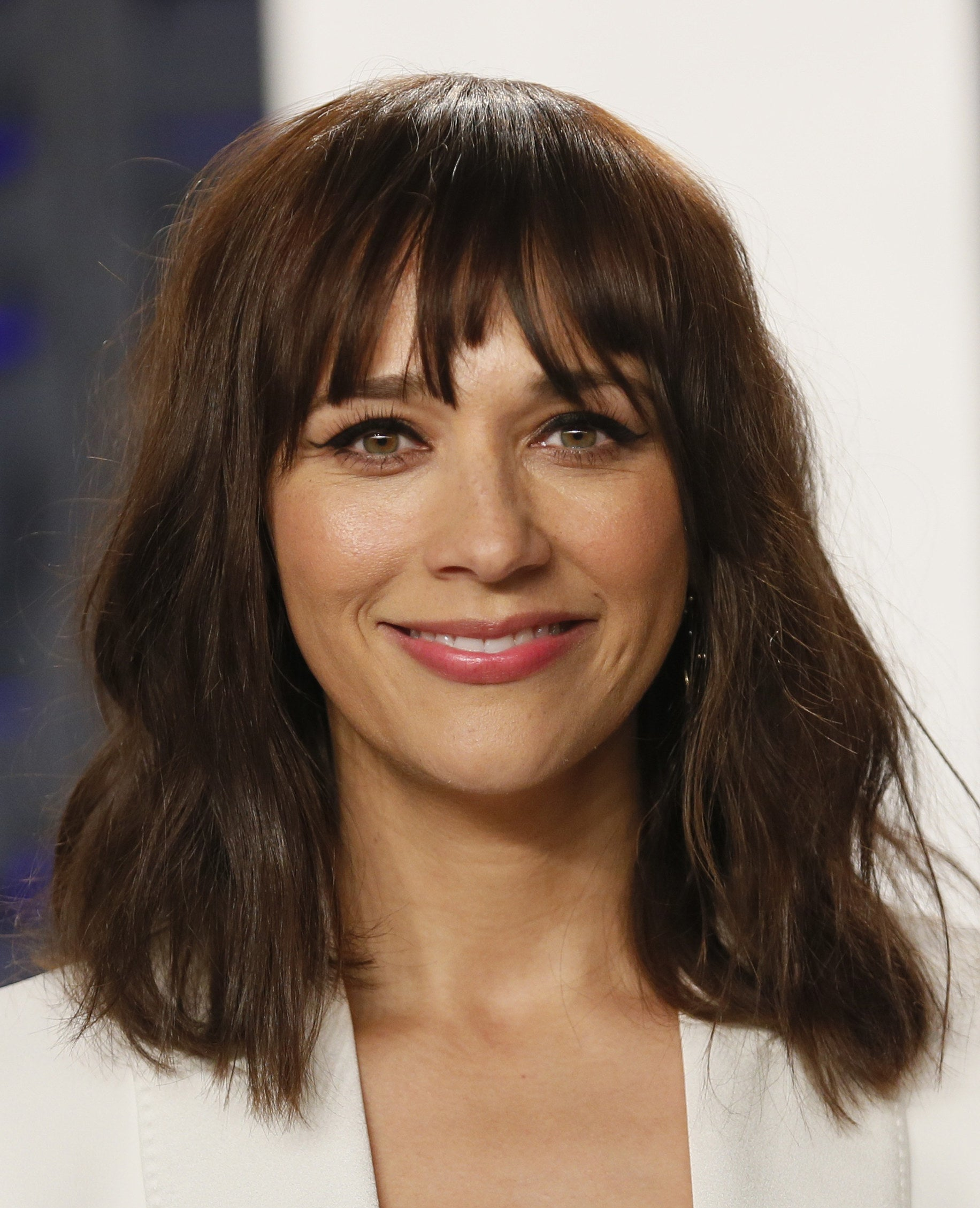 Rashida Jones with short wavy hair and bangs, smiling into the camera and wearing a blazer