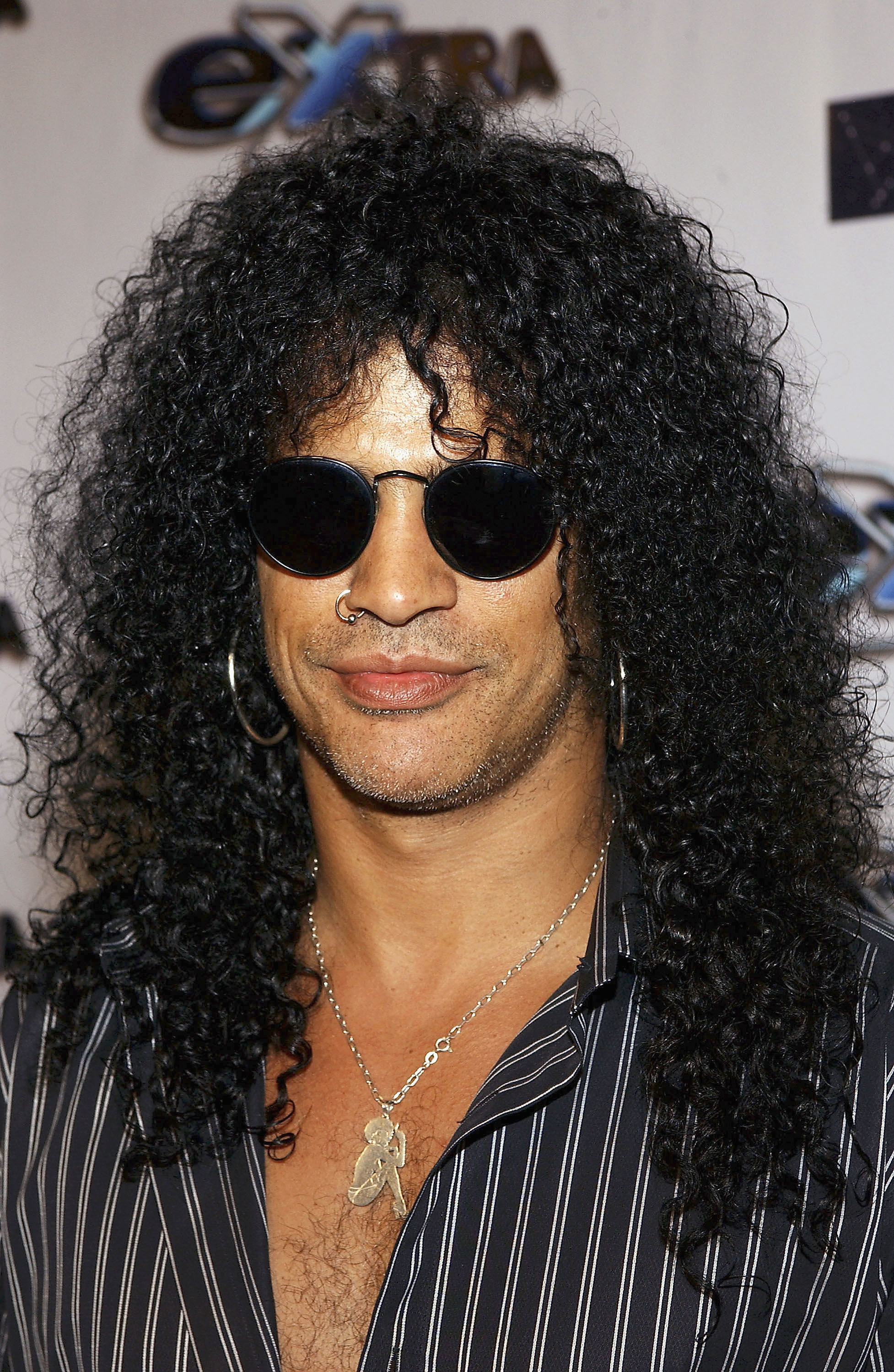 Slash smiling at the camera wearing his signature sunglasses, with his hair down and in a button-up top