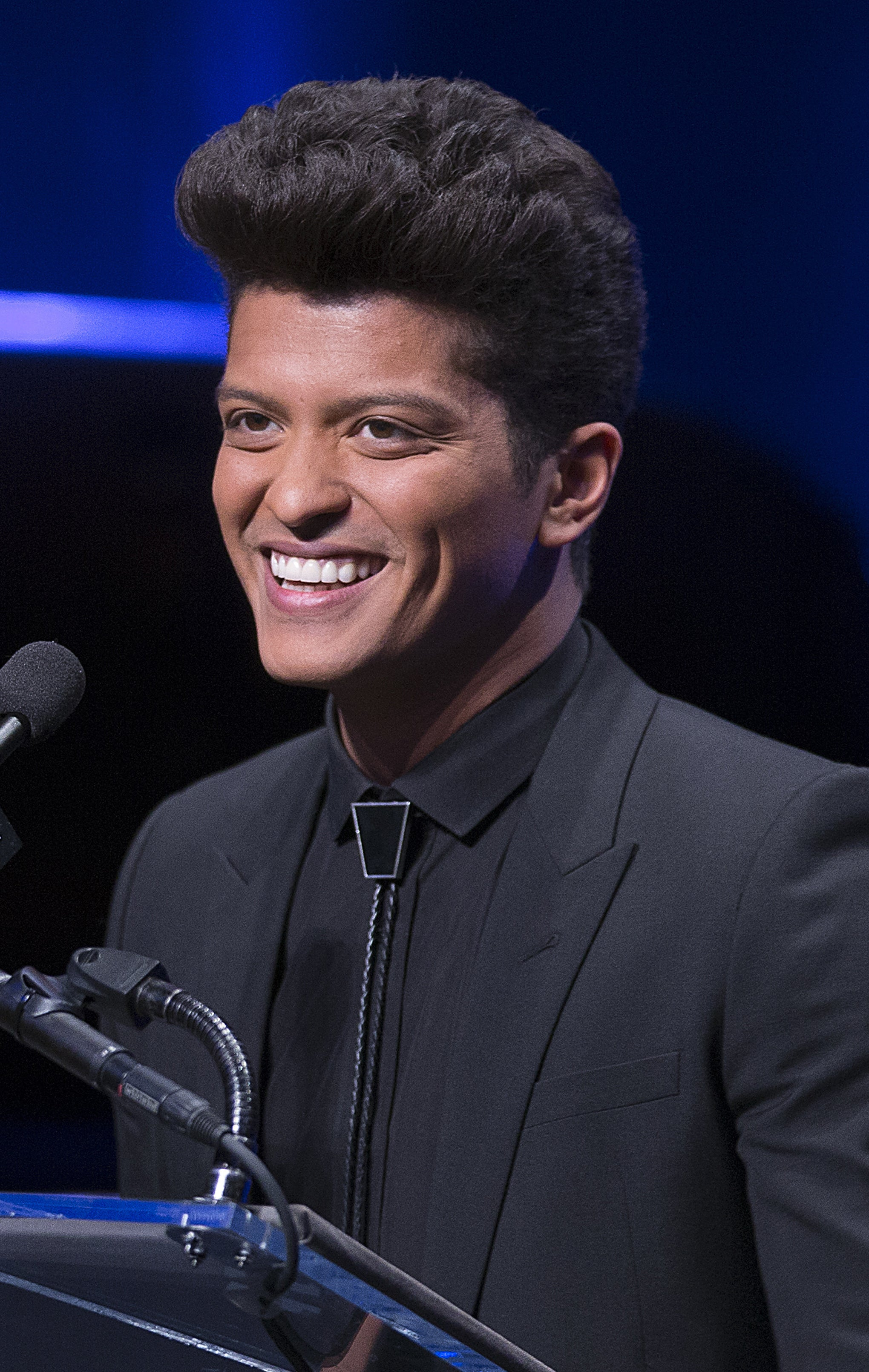 Bruno Mars giving a speech, wearing an all-black suit