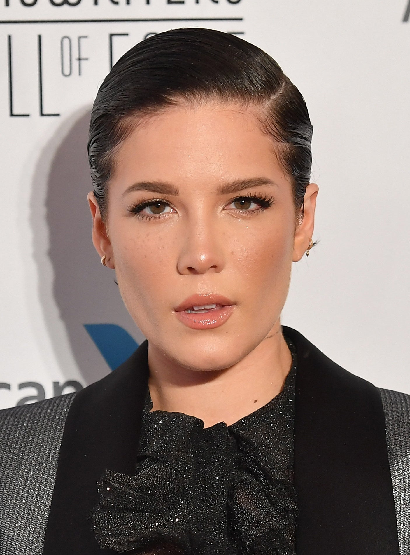 Halsey with a slicked-back pixie cut, looking directly into the camera