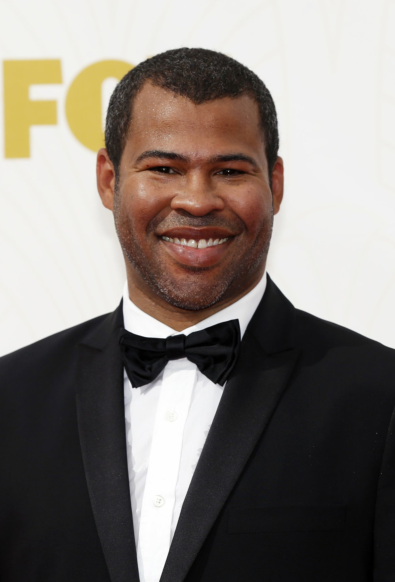 Jordan Peele smiling, wearing a black tux with a bow-tie