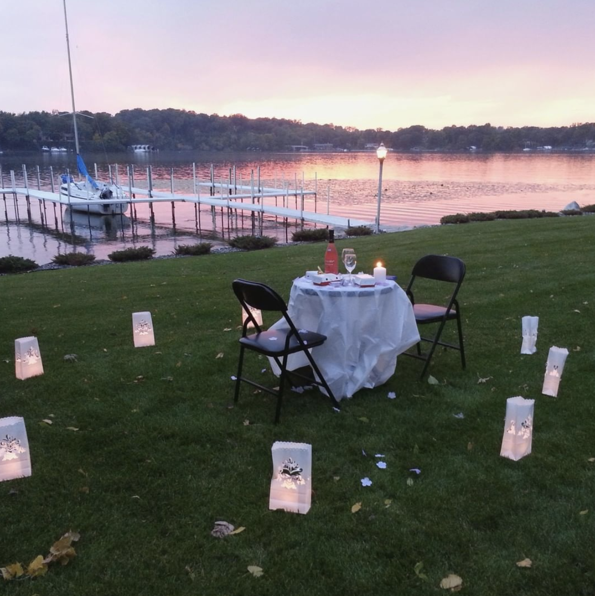 a romantic dinner table for two set up on a grassy lakeshore