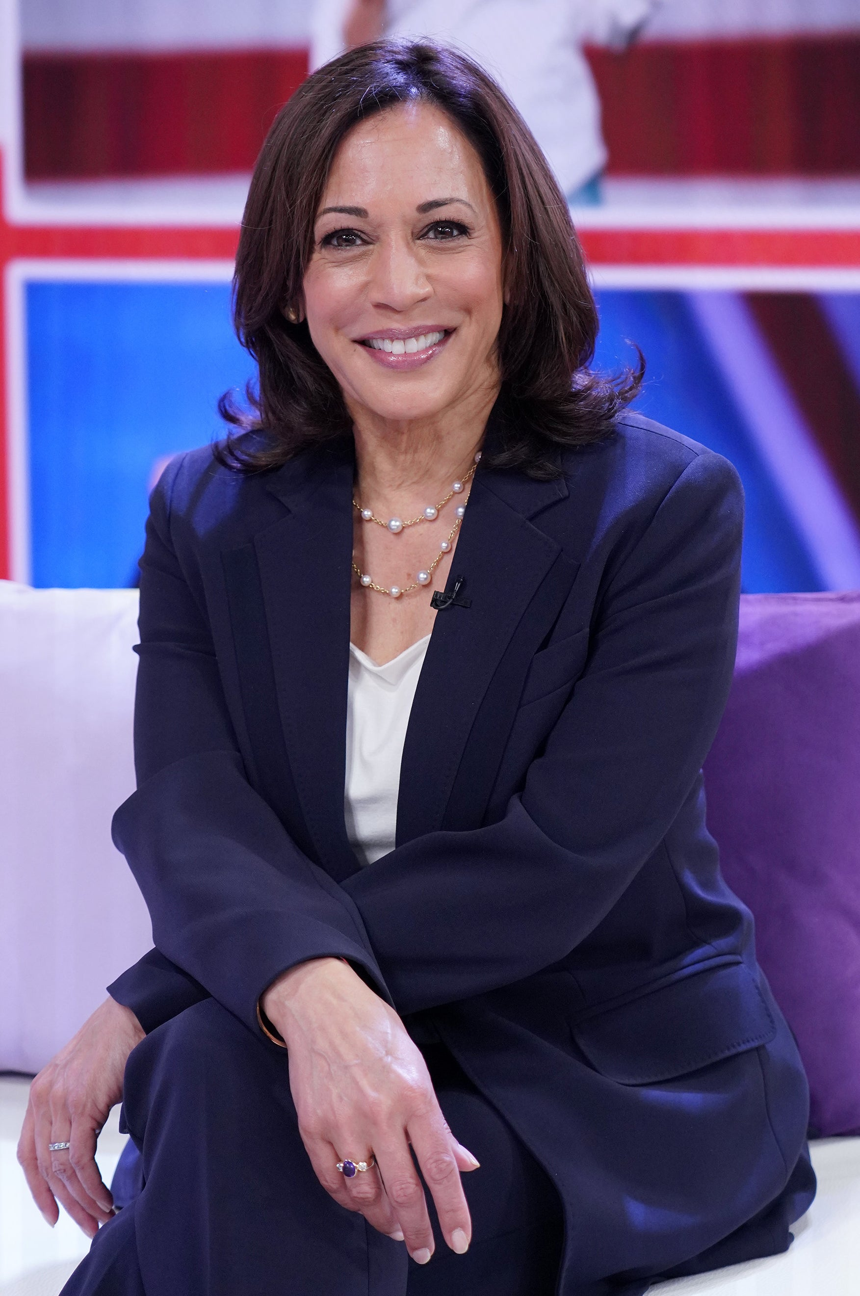 Kamala Harris smiling as she sits on a talk show couch in a navy blue suit with a white shirt