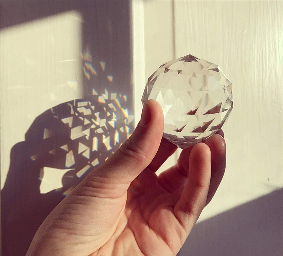 person holding the crystal with light shining through it