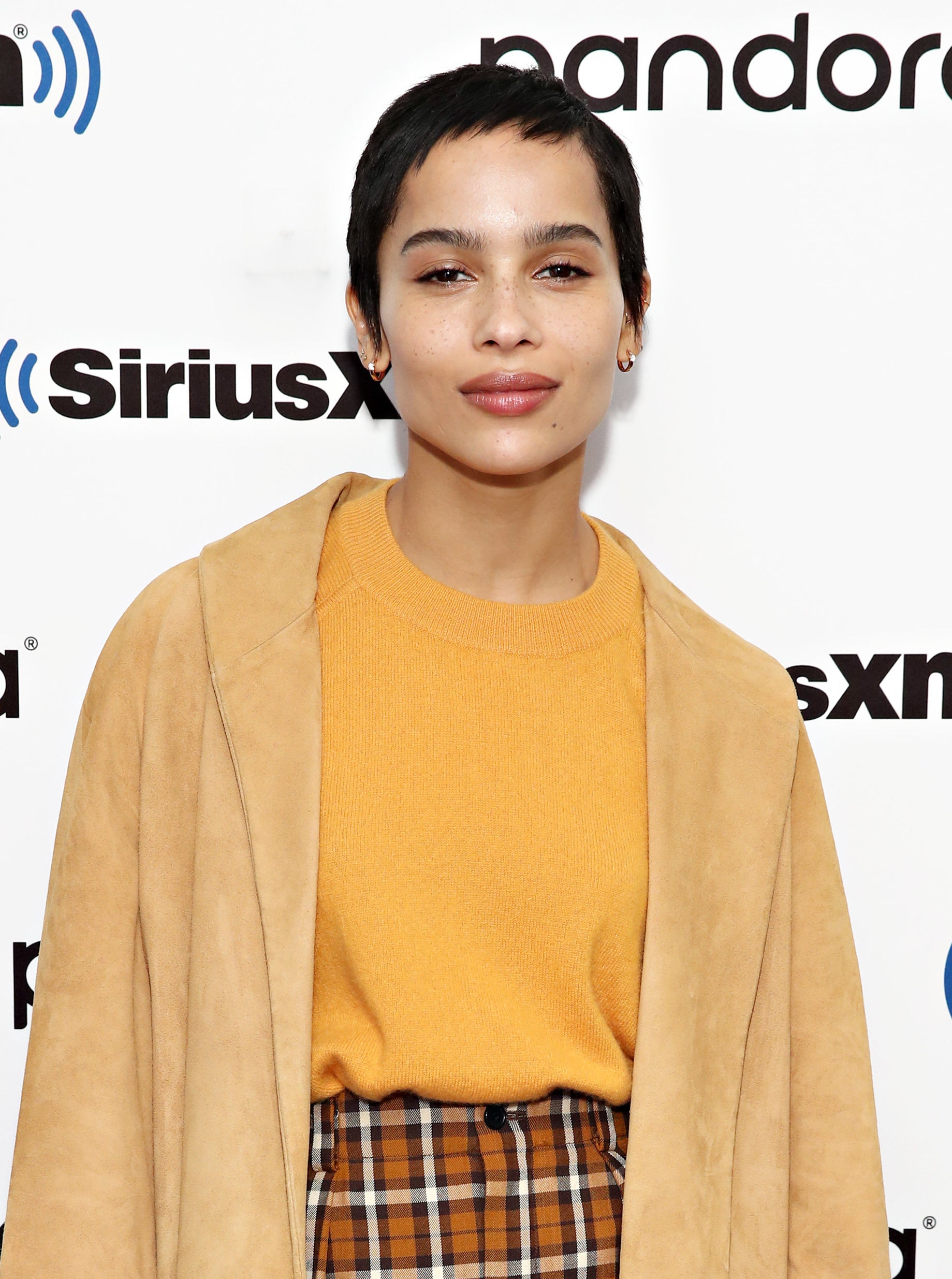 Zoe Kravitz at a red carpet event, with a pixie cut, wearing an orange sweater, plaid bands, and a coat
