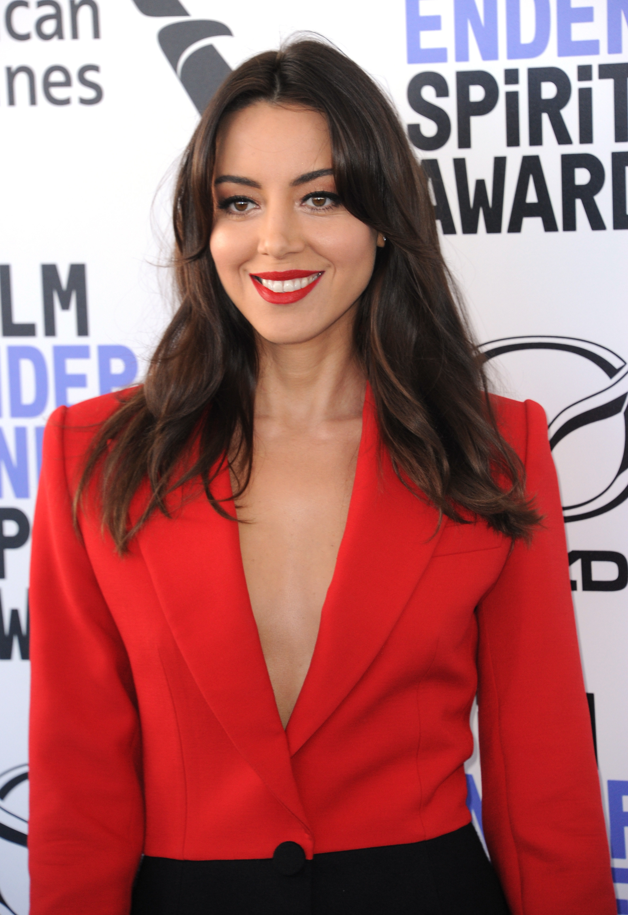 Aubrey Plaza wearing a red blazer with matching red lipstick