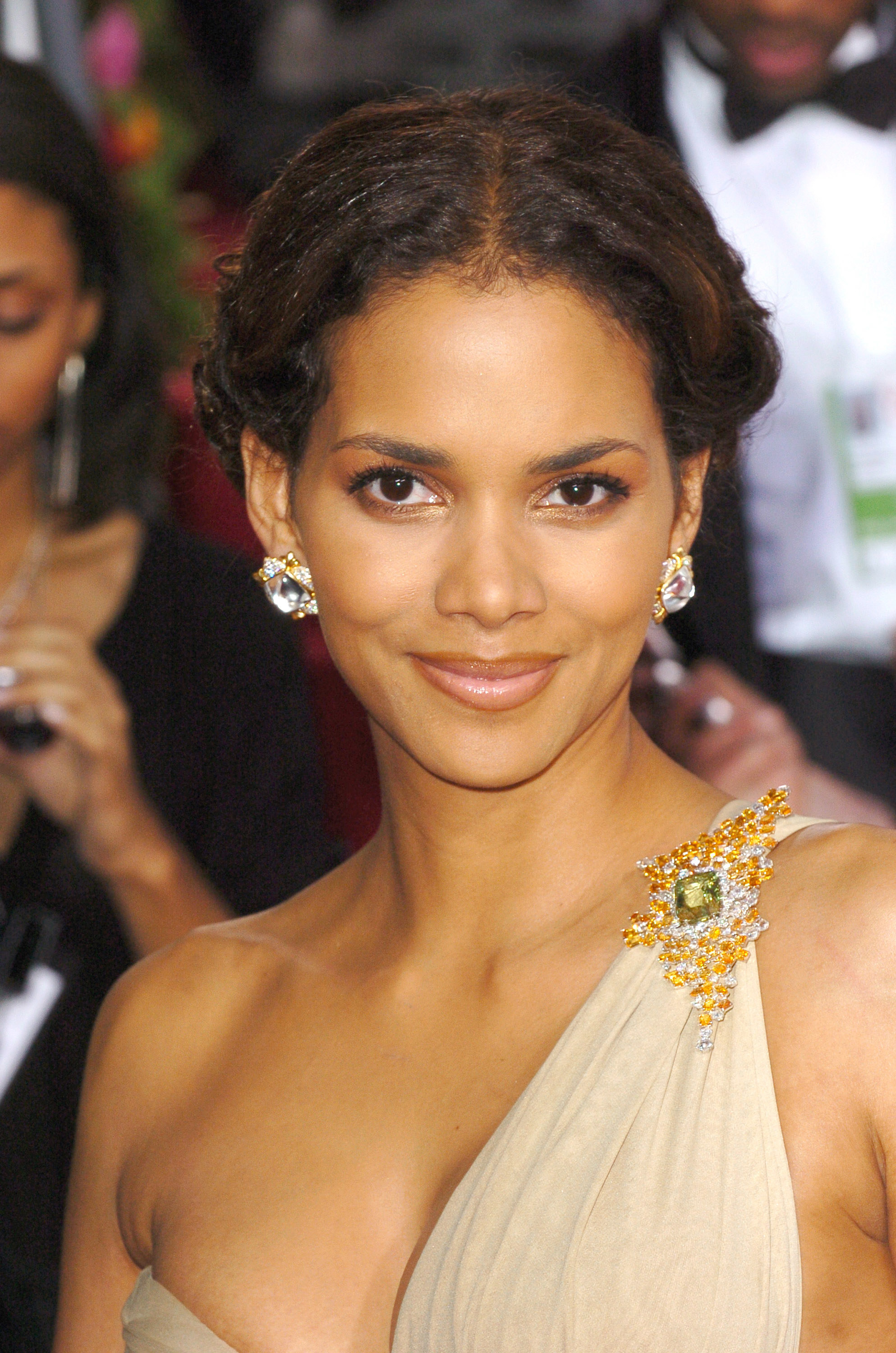 Halle Berry smiling, wearing a single shoulder toga-esque dress with a brooch and her hair pulled back