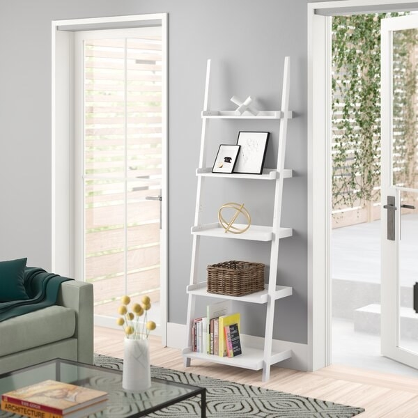 The bookcase in white, with five shelves that have the same width throughout but become shallower the higher you get on the ladder