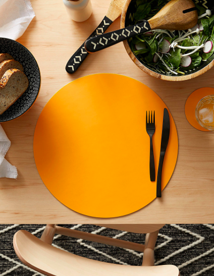 A flatlay of a circular placemat on a wooden dining table