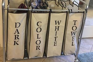 reviewer photo showing laundry organizer that they stenciled with the words dark, color, white, and towel