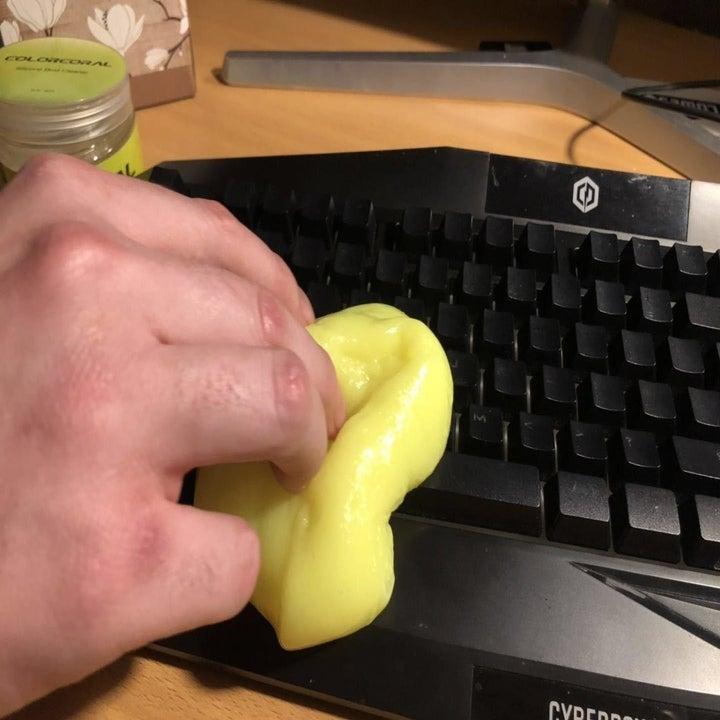 A reviewer photo of a hand pressing the slime against a black keyboard