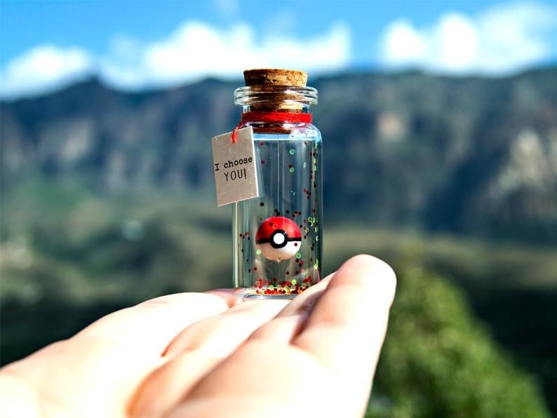 """A hand holding the corked bottle with glitter and a Poké Ball that looks like it's floating, with a tag that reads """"I choose you!"""""""