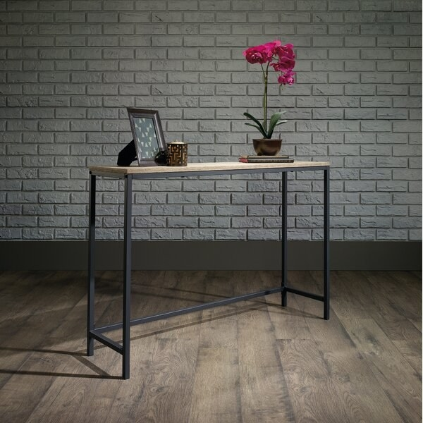The table, which has a thin rectangular wooden top, and a narrow black metal frame