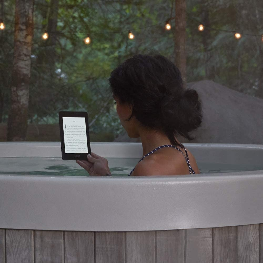 A person reading on the Kindle Paperwhite while in a hot tub