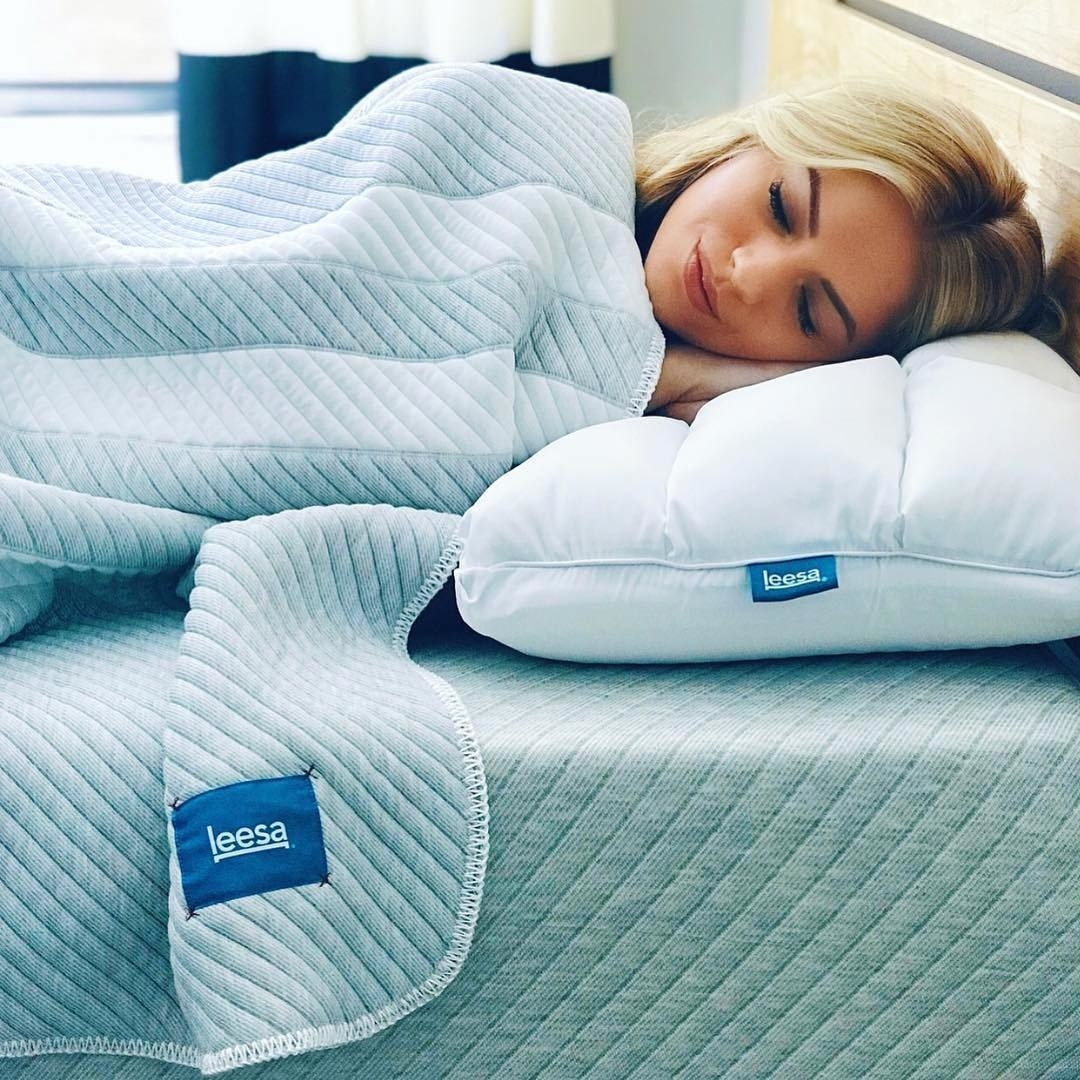 A smiling person sleeping on the adjustable pillow