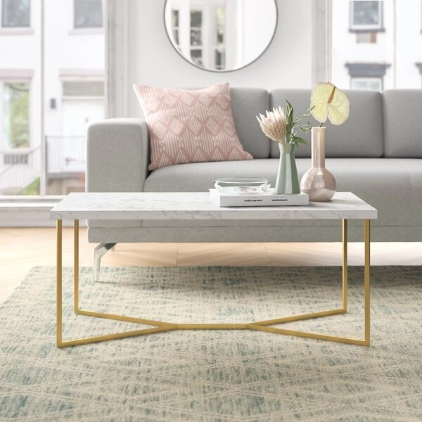 The coffee table, which has a rectangular wooden top with a marble print, and a frame that is shaped like an X on the ground