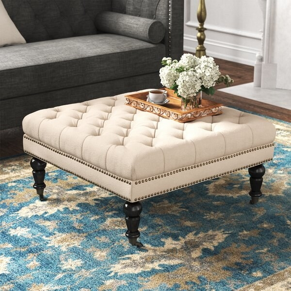 The ottoman, which has dark French country-style carved legs and a large, square tufted body, in beige