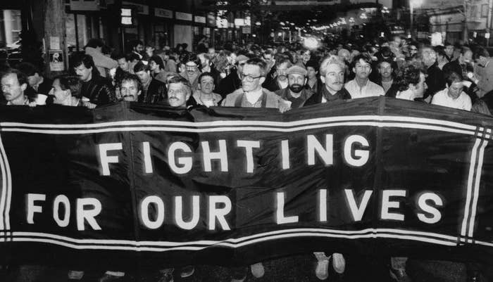 """Hundreds of men protest, holding up a large sign that says """"Fighting For Our Lives"""""""