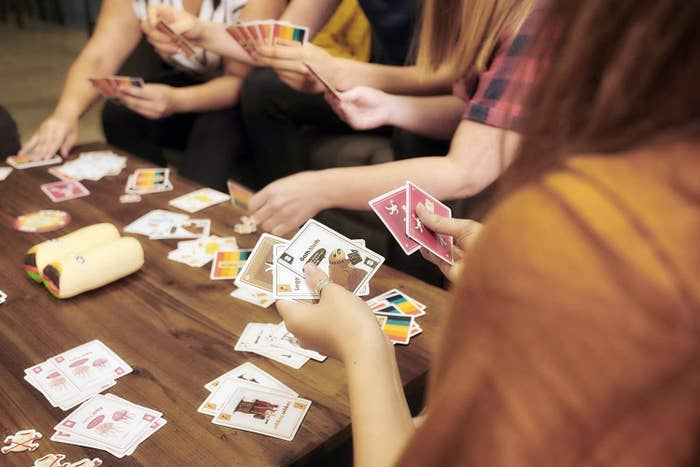 people around a table playing with the cards