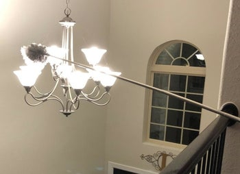 Amazon reviewer using duster to reach lamp hanging in the middle of a hallway