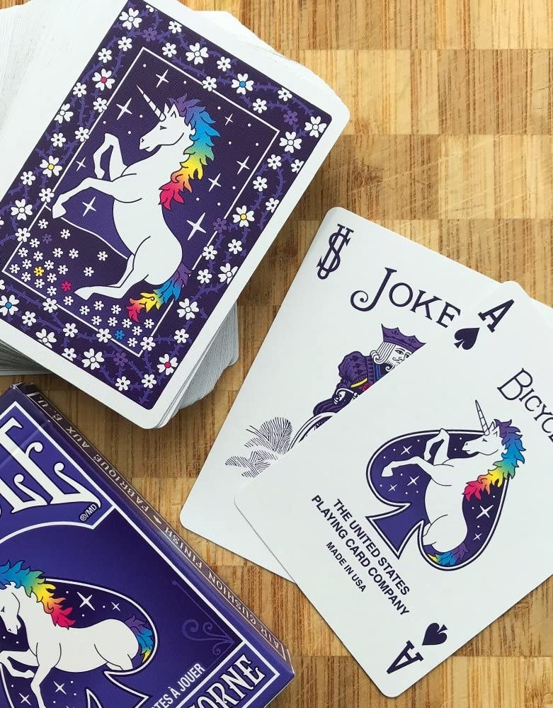 the back of the deck of cards showing a unicorn and a joker and ace
