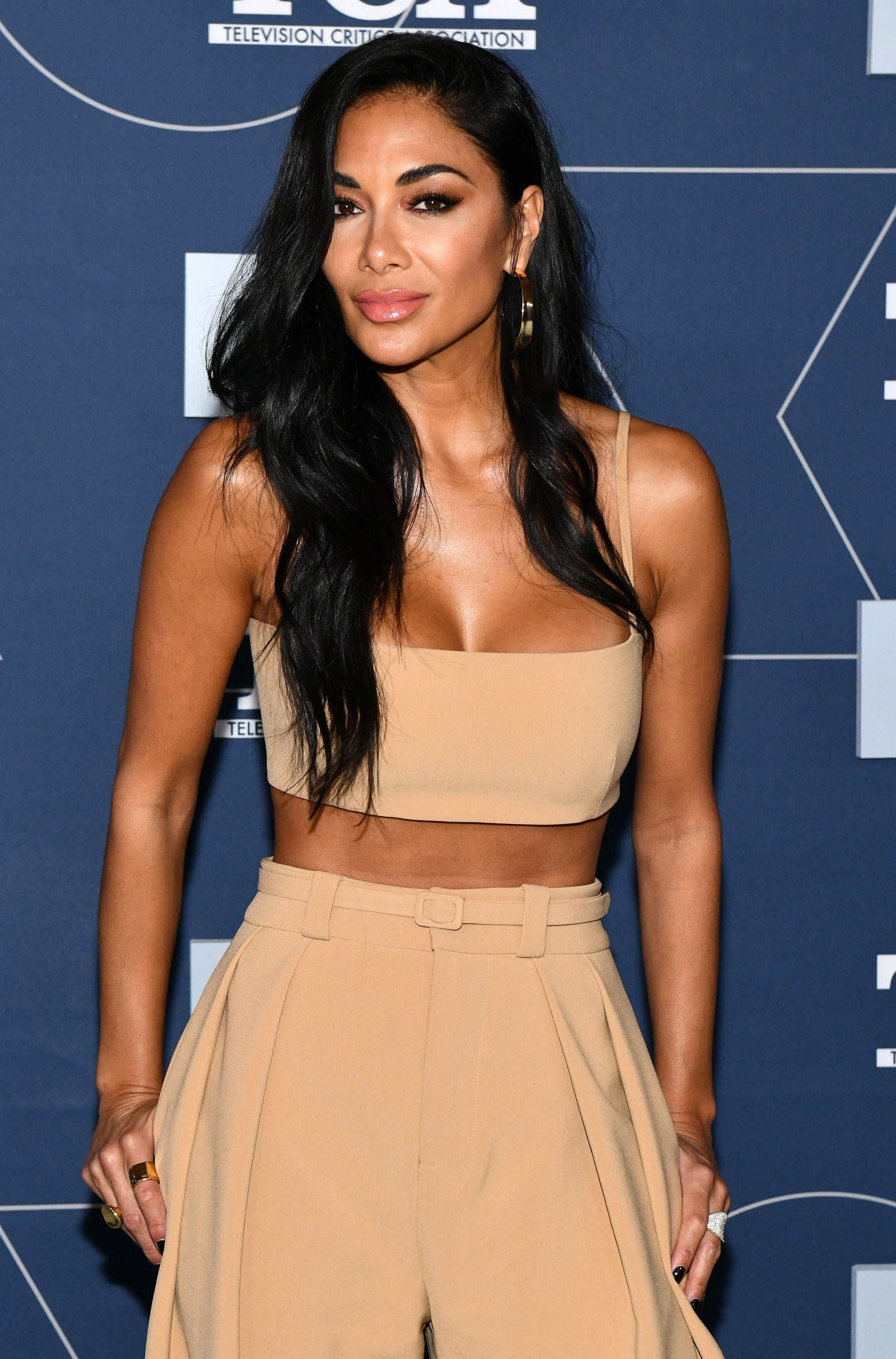 Nicole Scherzinger with her hair down and parted to the side, wearing a cropped nude top and matching pants