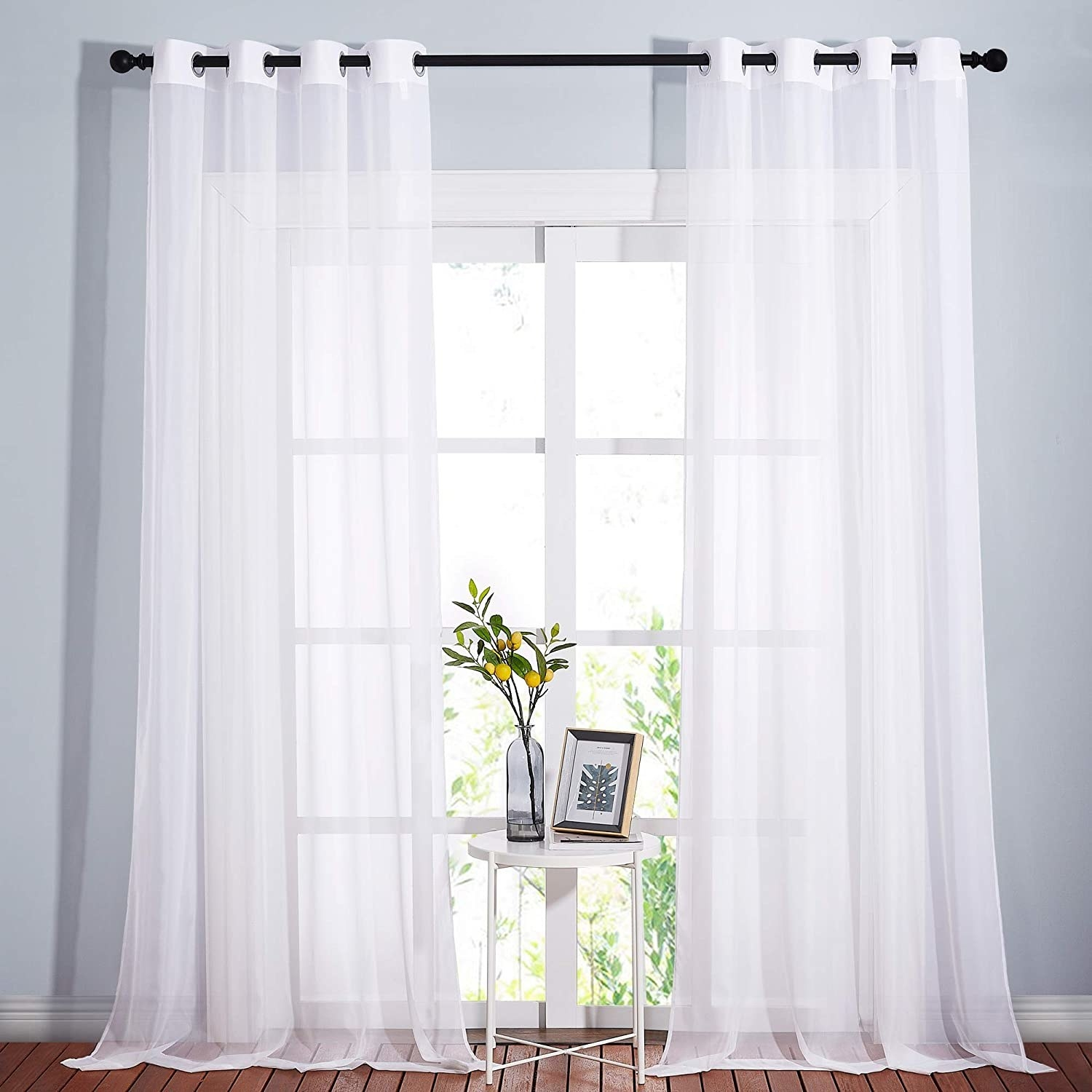 the curtains on a rod over a large window with a table in front of it