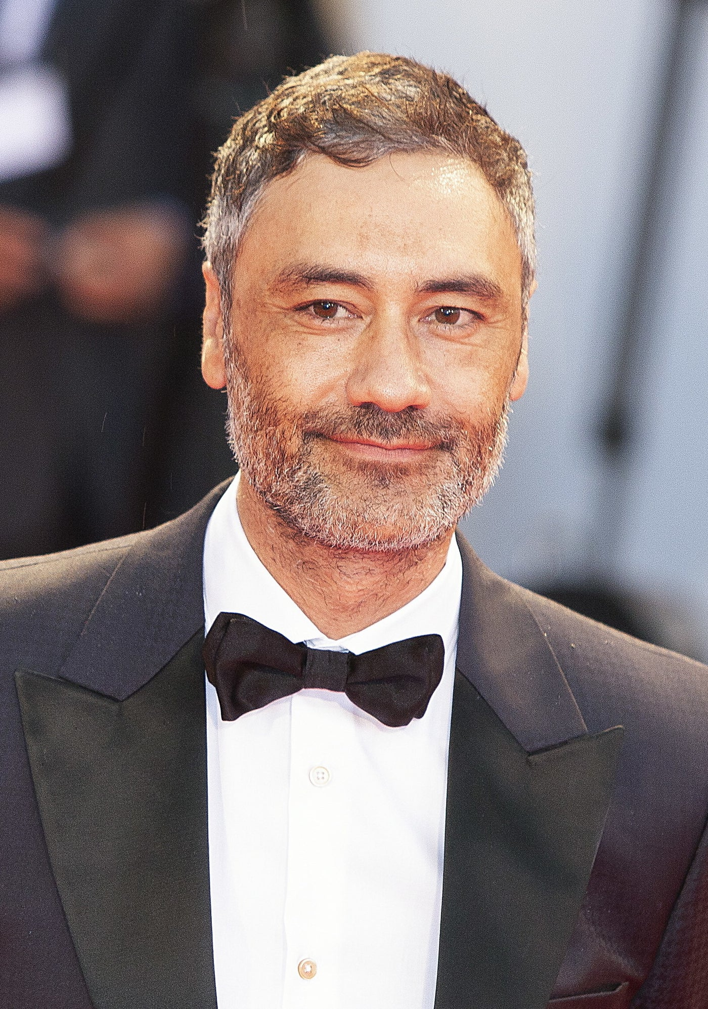 Taika Waititi in a suit with a bow-tie