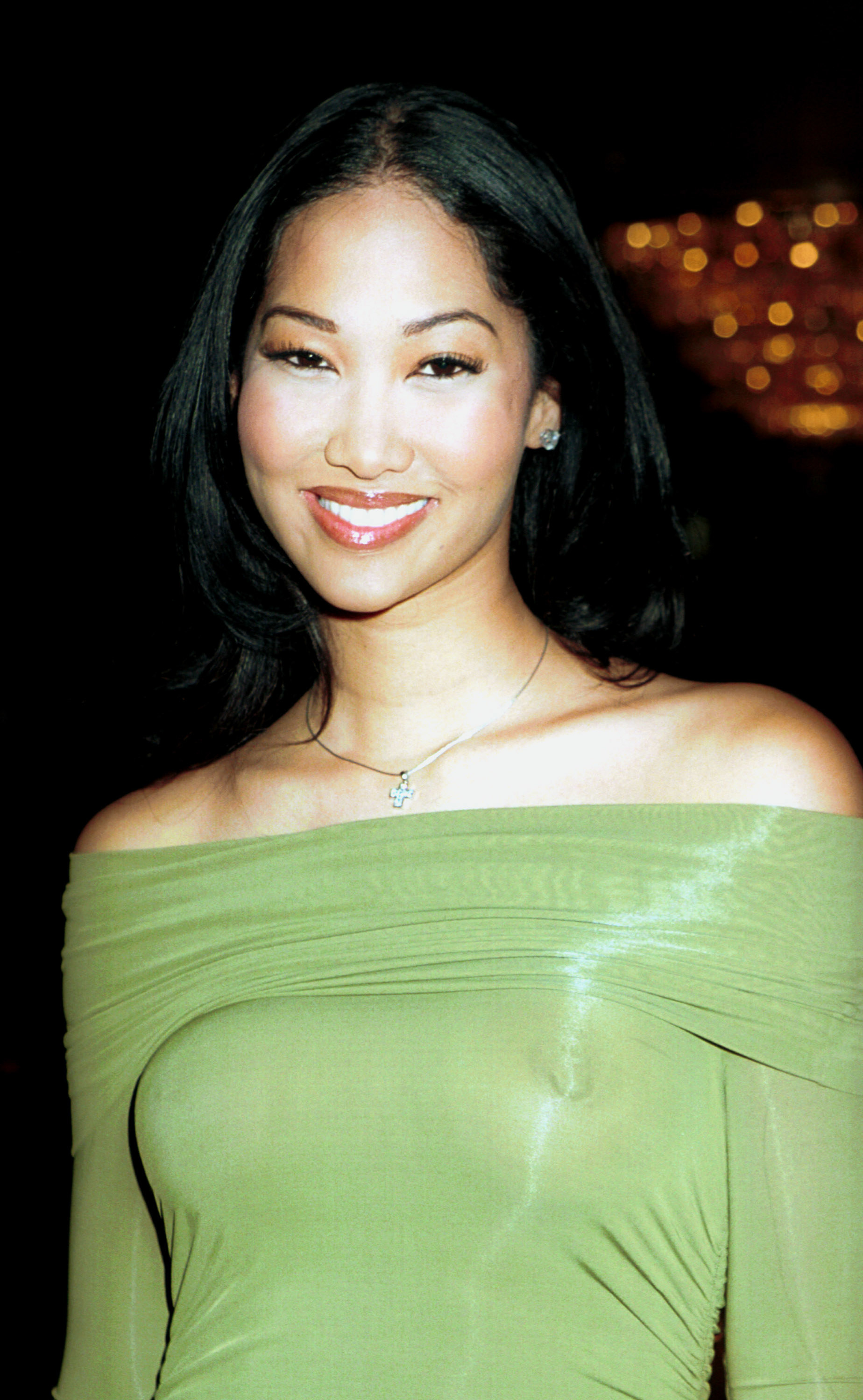 Kimora Lee Simmons with her hair down and straight, wearing a sheer green dress