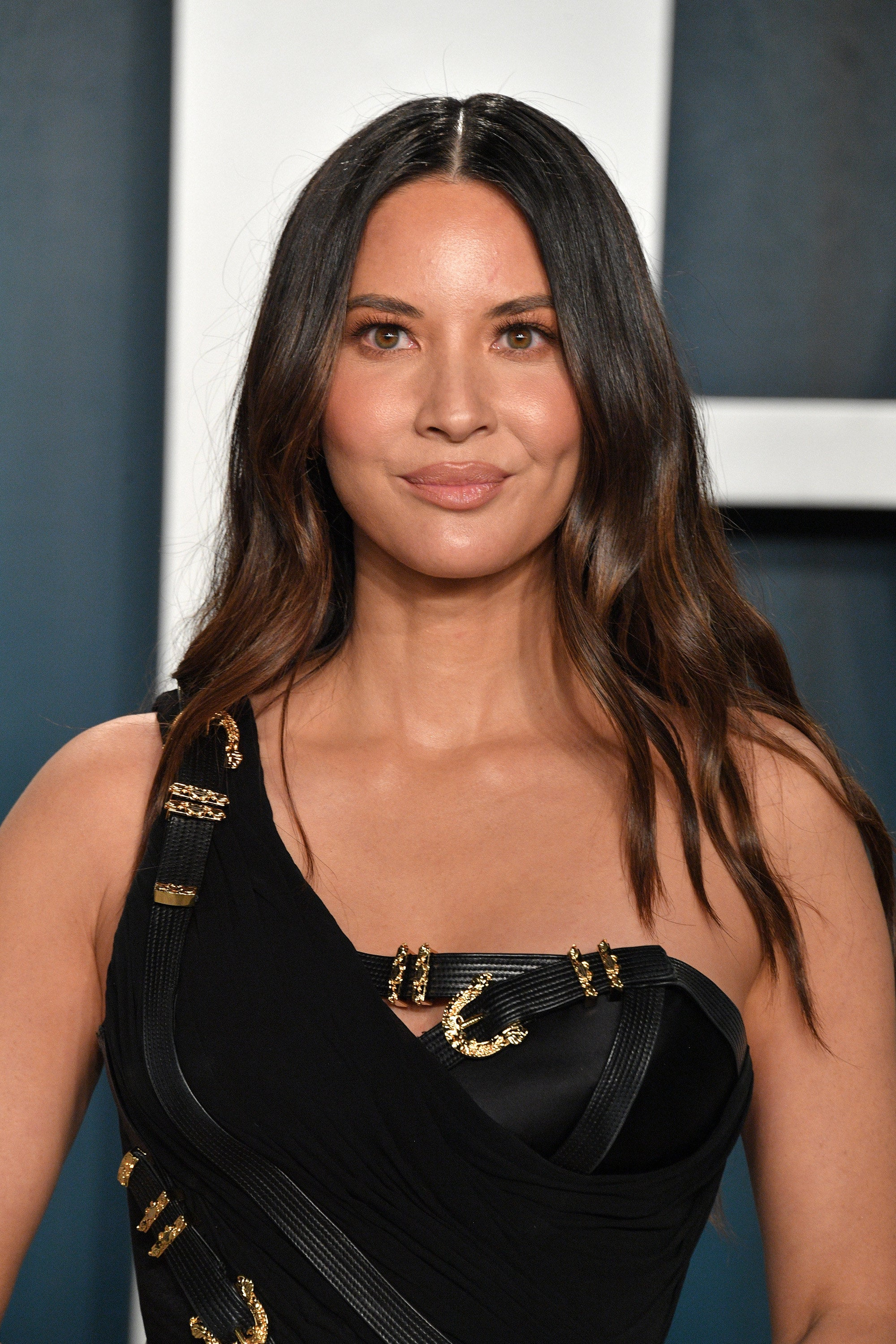 Olivia Munn smiling, wearing a single-shoulder, black dress embellished with gold buckles