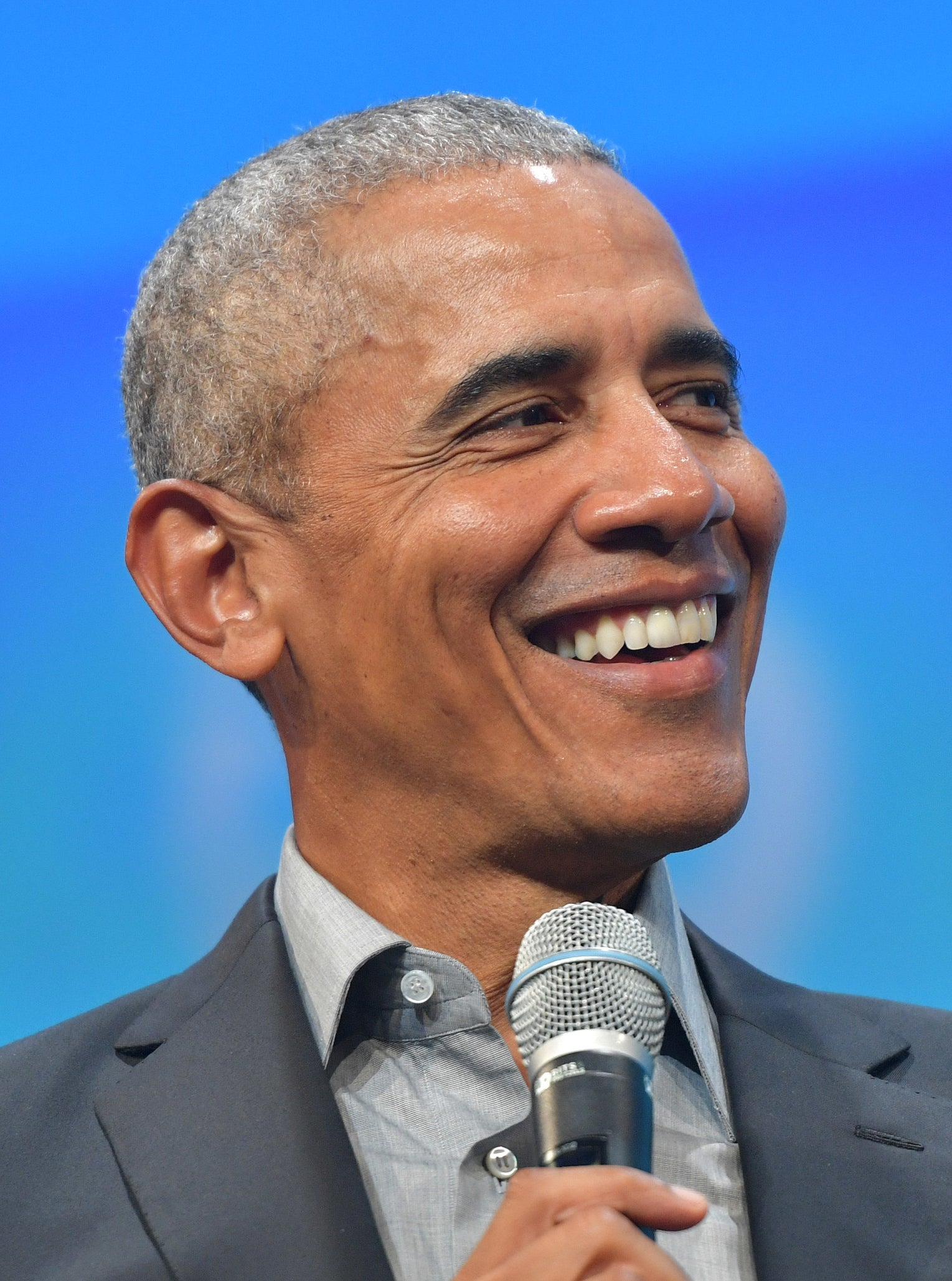 President Obama smiling as he holds a mic, wearing a suit