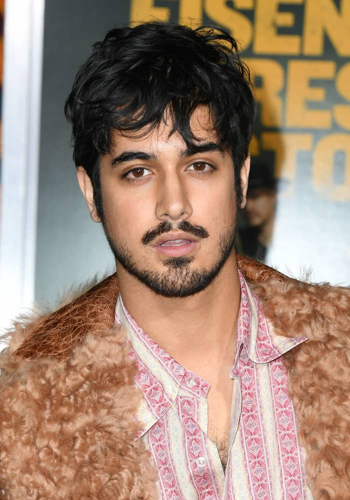 Avan Jogia with short hair wearing a teddy coat and button down shirt